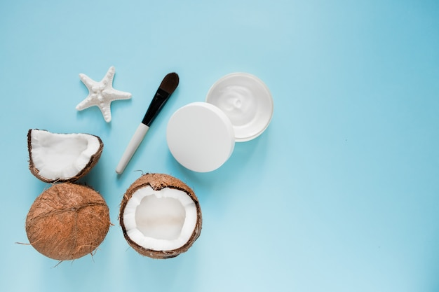 Geopende glazen pot met verse kokosolie en rijpe kokosnoten op blauw