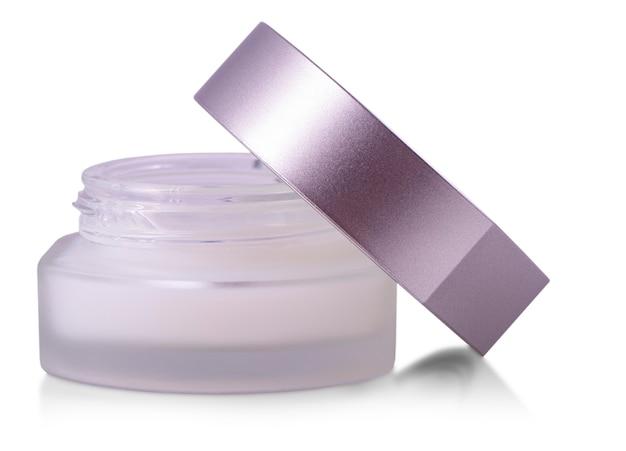 Geopende glazen pot schoonheidscrème met dop op wit wordt geïsoleerd