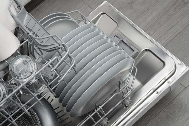 Geopende huishoudelijke vaatwasser met gereinigd servies
