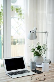 Geopende laptop met leeg scherm, kopje koffie en vaas met bloeiende bloemen op bureau van zakelijke persoon