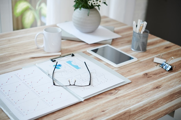 Geopende map met verkooprapporten en glazen op tafel van ondernemer