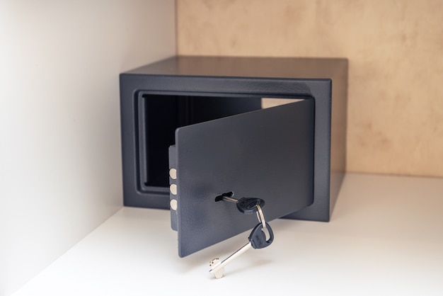 Geopende metalen kluis met sleutel en geopende deur in de hotelkamer, in de kast