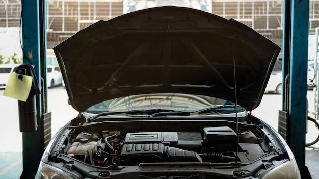 Geopende motorkap bij het reparatiestation, reparatieservices en onderhoud