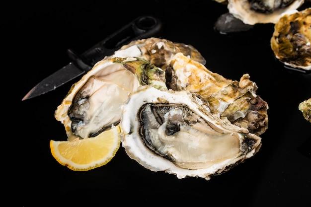 Geopende oesters, ijs en citroen op een zwarte ondergrond