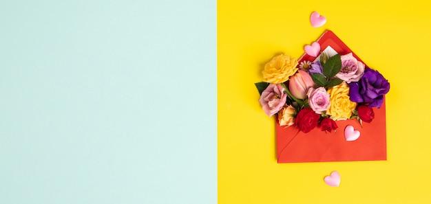 Geopende rode envelop met bloemenregelingen op gele achtergrond