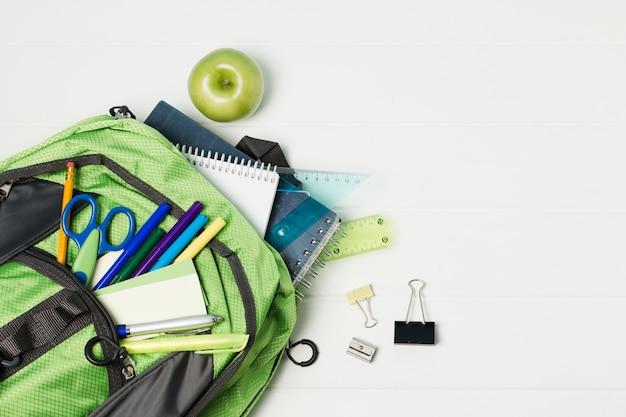 Geopende rugzak met het bovenaanzicht van schooltoebehoren