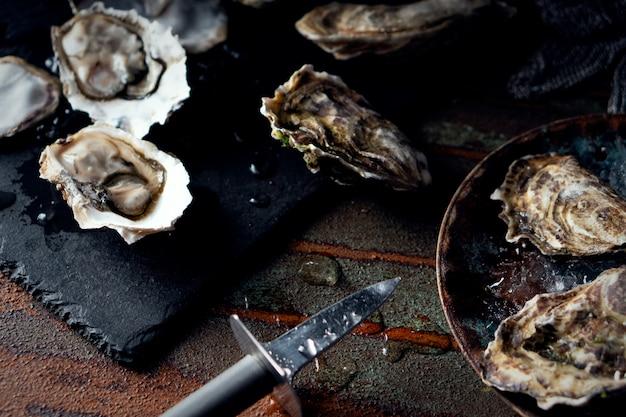 Geopende verse oesters op een donkere achtergrond, een mes en waterdruppels. rostik stijl.