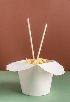 Geopende wok-kartonnen doos met noedels en eetstokjes voor mock-upontwerp