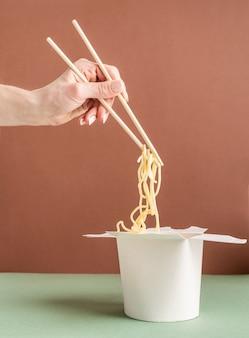 Geopende wok-papieren doos voor mock-upontwerp. vrouw hand met noedels met stokjes