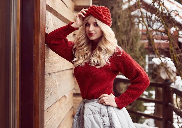 Georgeous elegante blonde in rode jurk en hoed