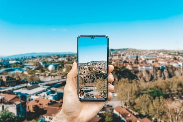 Georgië en tbilisi maken een landschap van een hand met een smartphone die de bezienswaardigheden van georgië en tbilisi fotografeert