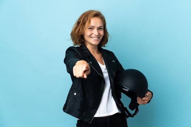 Georgisch meisje dat een motorhelm houdt die op blauwe achtergrond wordt geïsoleerd die voorzijde met gelukkige uitdrukking richt