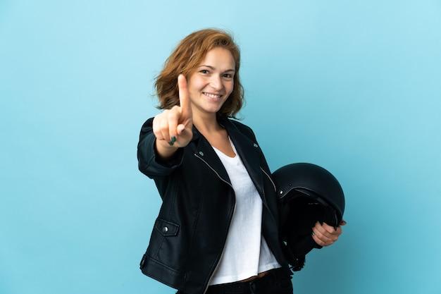 Georgisch meisje met een motorhelm geïsoleerd op een blauwe achtergrond die een vinger laat zien en optilt
