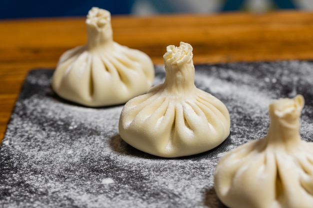 Georgische dumplings khinkali met vlees op een houten bord met bloem zwarte achtergrond proces van makin...