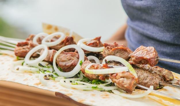 Georgische kebabs in de handen van mannen