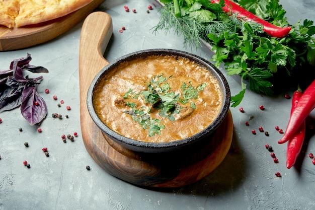 Georgische keuken - groene kharcho met rundvlees, rijst en pruimensaus