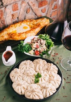 Georgische khinkali met saladesaus en tandirbrood.