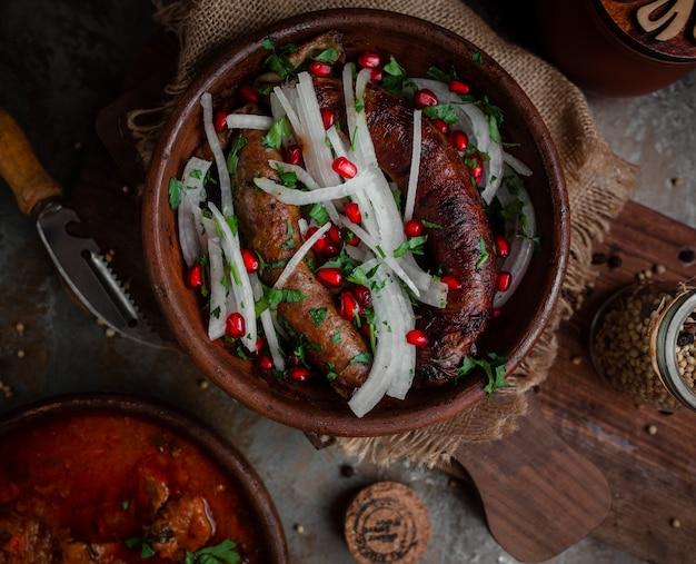 Georgische kupat met uien en granaatappel in aardewerk