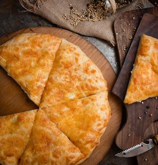 Georgische pizzakhachapuri die op een gesmolten kaas wordt gesneden.
