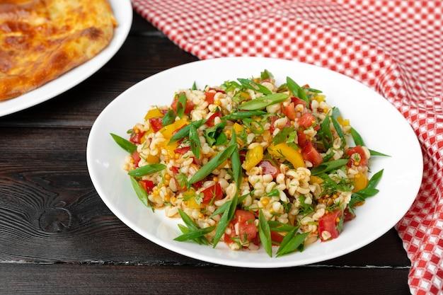 Georgische tabouleh salade met bulgur en groenten op zwarte houten tafel close-up
