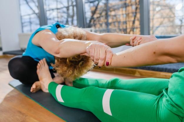 Gepaarde vrouwelijke fitnesstraining yoga, twee vrouwen zitten op de vloer en maken samen rekoefeningen
