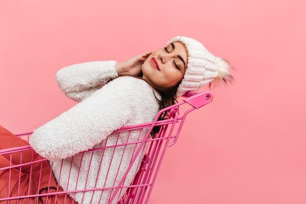 Gepacificeerd meisje met gesloten ogen poseert in roze trolley. portret van dame in warme muts en trui.