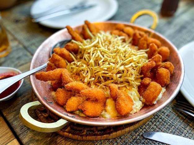 Gepaneerde garnalen met knapperig meel en sesam, met prei-risotto en stro-aardappelen.