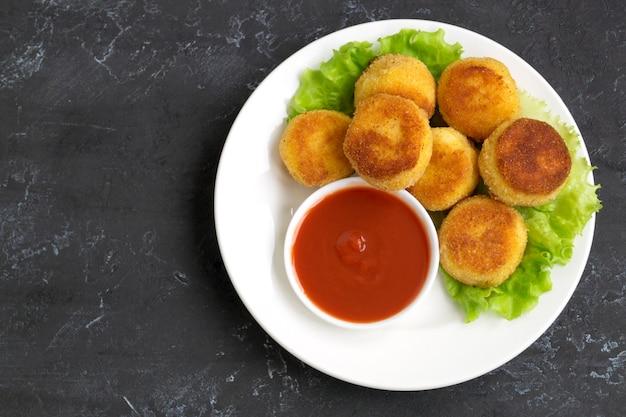 Gepaneerde gebakken aardappelballetjes met tomatensaus
