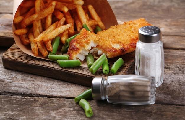 Gepaneerde gebakken visfilet en aardappelen in papieren zak met asperges op snijplank en rustieke houten