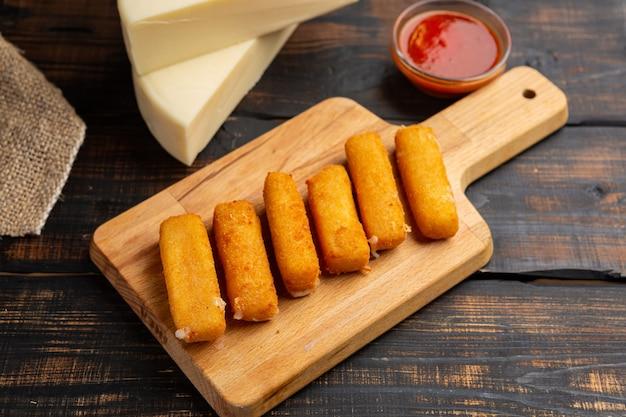 Gepaneerde mozzarella kaasstengels met ketchupsaus op houten snijplank