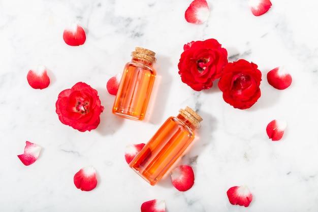 Geparfumeerd rozenwater in glazen fles en kleine rode rozen met bloemblaadjes.