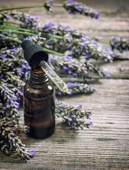 Geparfumeerde kruidenolieessentie en lavendelbloemen over rustieke houten achtergrond. vintage foto