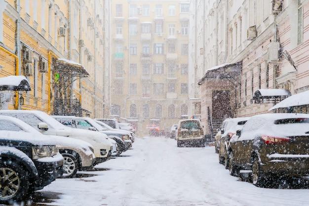 Geparkeerde auto's bedekt met sneeuw in de stadswijk stadsgezicht f