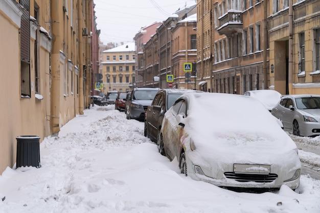 Geparkeerde auto's bedekt met sneeuw op een ongereinigde besneeuwde weg na sneeuwval. slecht winterweer, meer neerslag en sneeuwniveaus concept.