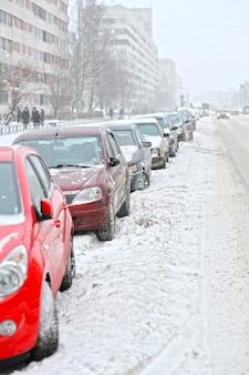 Geparkeerde auto's langs de weg in de winter