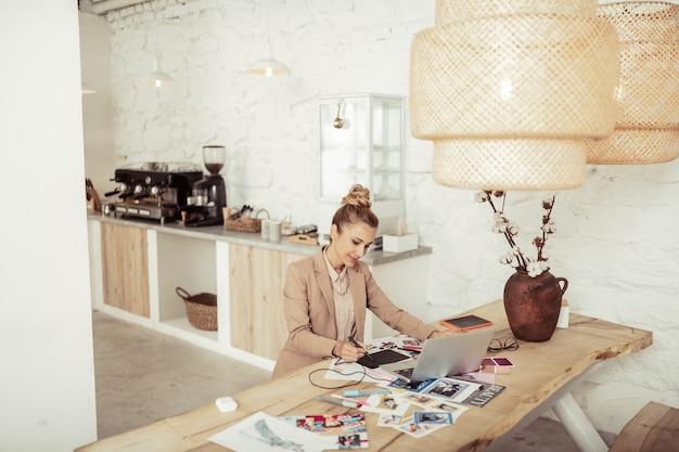 Gepassioneerd door werk. lachende mooie dame zittend aan de tafel voor haar laptop en bezig met haar kledingontwerpen.
