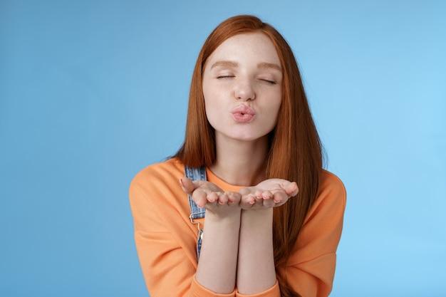 Gepassioneerd dromerig mooi roodharig meisje zendt luchtkussen camera ogen sluiten ogen vouwen lippen handen vasthouden in de buurt van mond geven muah internet volgers opname vlog staand romantische tedere blauwe achtergrond