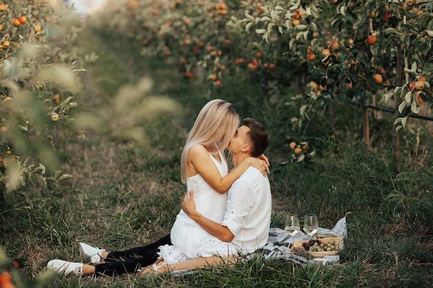 Gepassioneerd paar knuffelt zittend op de picknickkleed op datum. daarnaast picknickmand met druiven en croissants en wijnglazen.