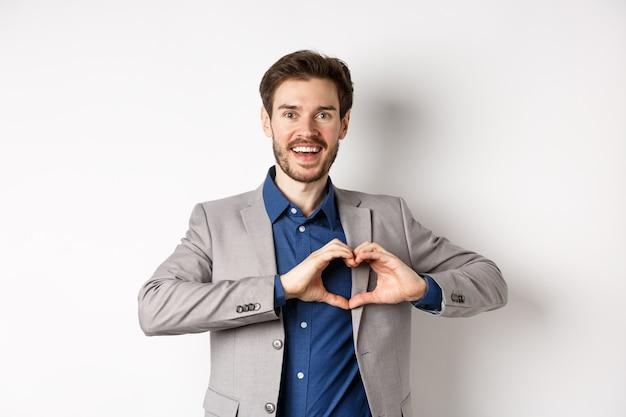 Gepassioneerde en romantische man in pak verliefd worden, hart teken tonen en glimlachen naar minnaar, staande op een witte achtergrond.