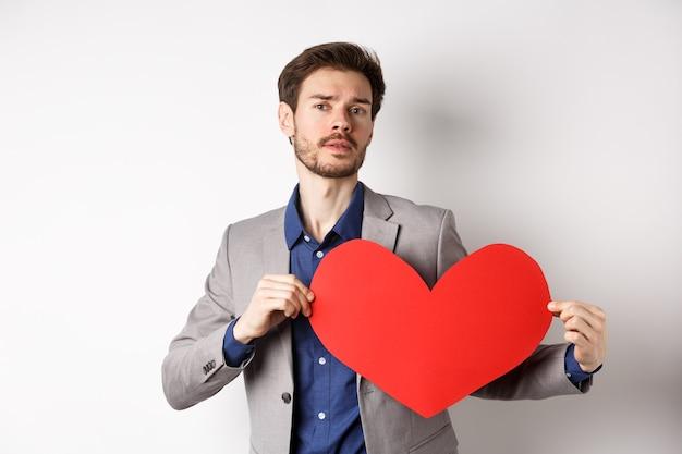 Gepassioneerde knappe man met hart bonzend gebaar met rode valentines knipsel, permanent in pak en op zoek naar liefde, staande op witte achtergrond.