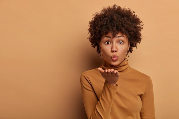 Gepassioneerde knappe vrouw met afro-kapsel blaast airkiss