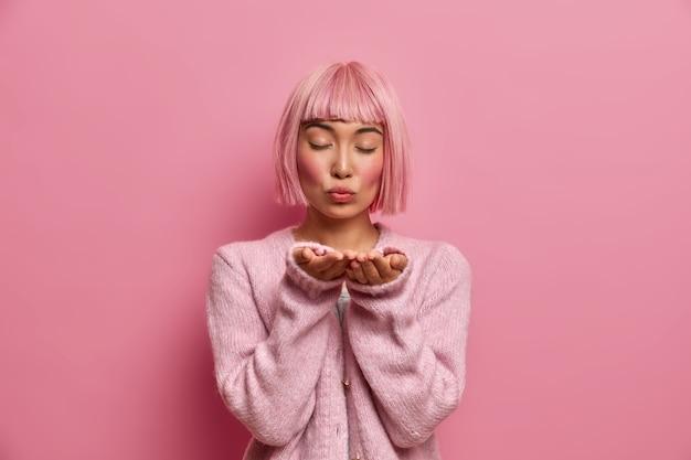 Gepassioneerde tedere aziatische dame stuurt luchtkus met gevouwen lippen, staat met gesloten ogen, heeft roze bob kapsel, gekleed in warm, comfortabel zweet