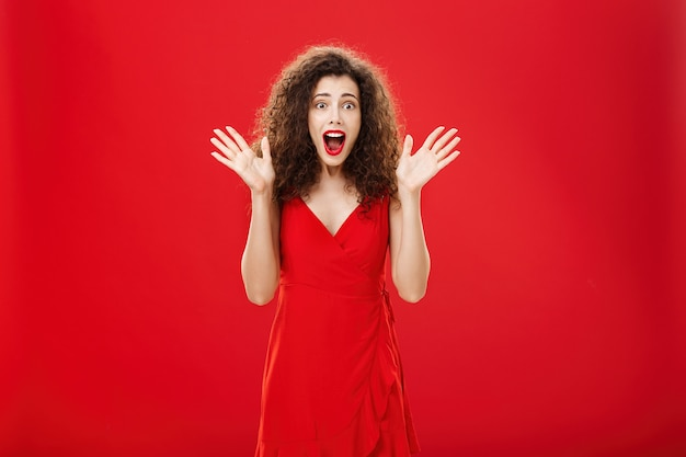 Gepassioneerde verbaasde en opgewonden europese volwassen vrouw in avondjurk met krullend kapsel schreeuwen ...
