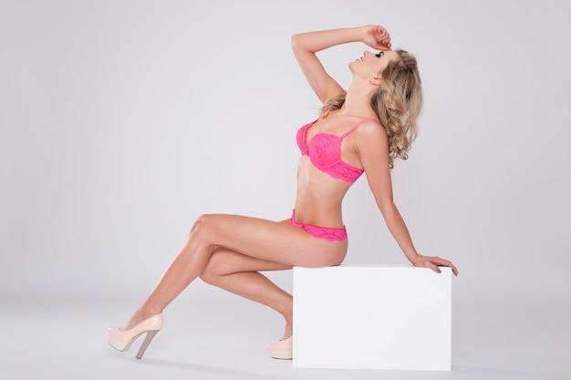Gepassioneerde vrouw in sexy lingerie zittend op het whiteboard