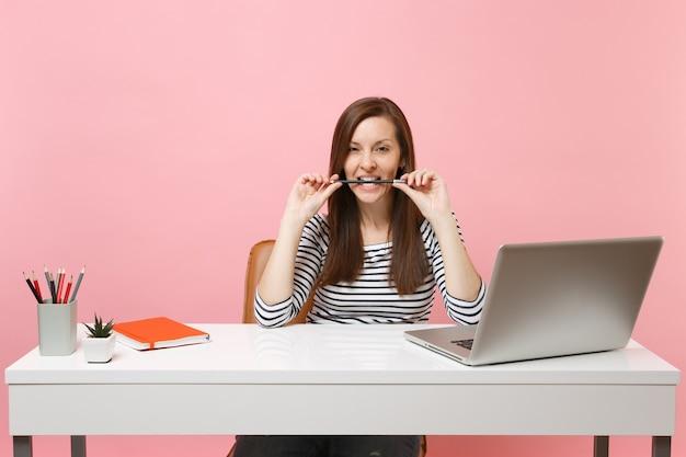 Gepassioneerde vrouw in vrijetijdskleding knaagt aan een potlood in tanden en zit aan het werk aan een wit bureau met een moderne pc-laptop