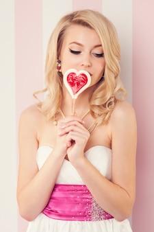 Gepassioneerde vrouw met lolly in hartvormig