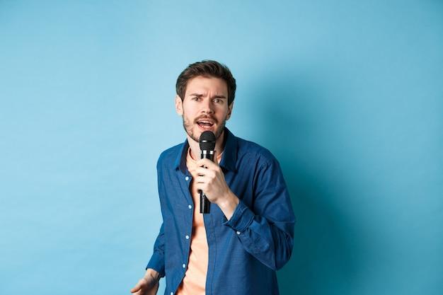 Gepassioneerde zanger camera kijken, zingen in de microfoon, karaoke spelen op blauwe achtergrond. kopieer ruimte