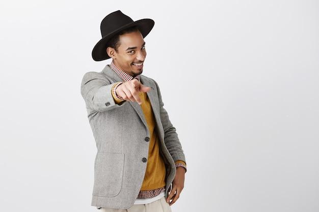 Gepassioneerde zelfverzekerde donkere man die voor jou kiest. portret van charmante afro-amerikaan in modieuze hoed en jas, hand trekken en met sensuele flirterige glimlach wijzen over grijze muur