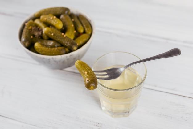 Gepekeld sap, augurk en gemarineerde komkommer in een kom. schoon eten, vegetarisch voedselconcept