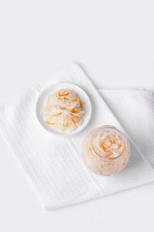 Gepekelde kool en wortel op een bord, naast een pot marinade. gefermenteerde levensmiddelen. witte achtergrond.
